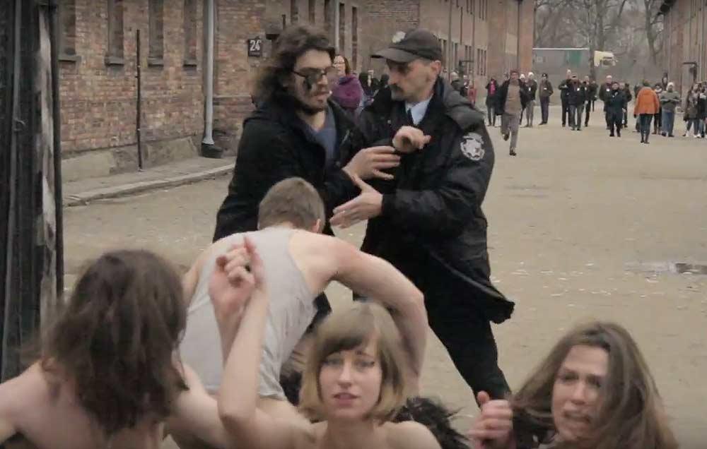 Nadzy manifestanci przed wejściem do Auschwitz